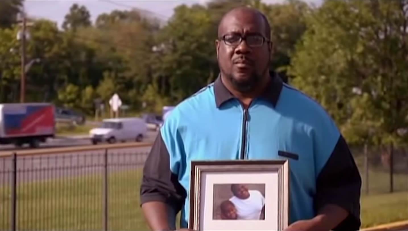 John Howard holding a photo of his missing boys